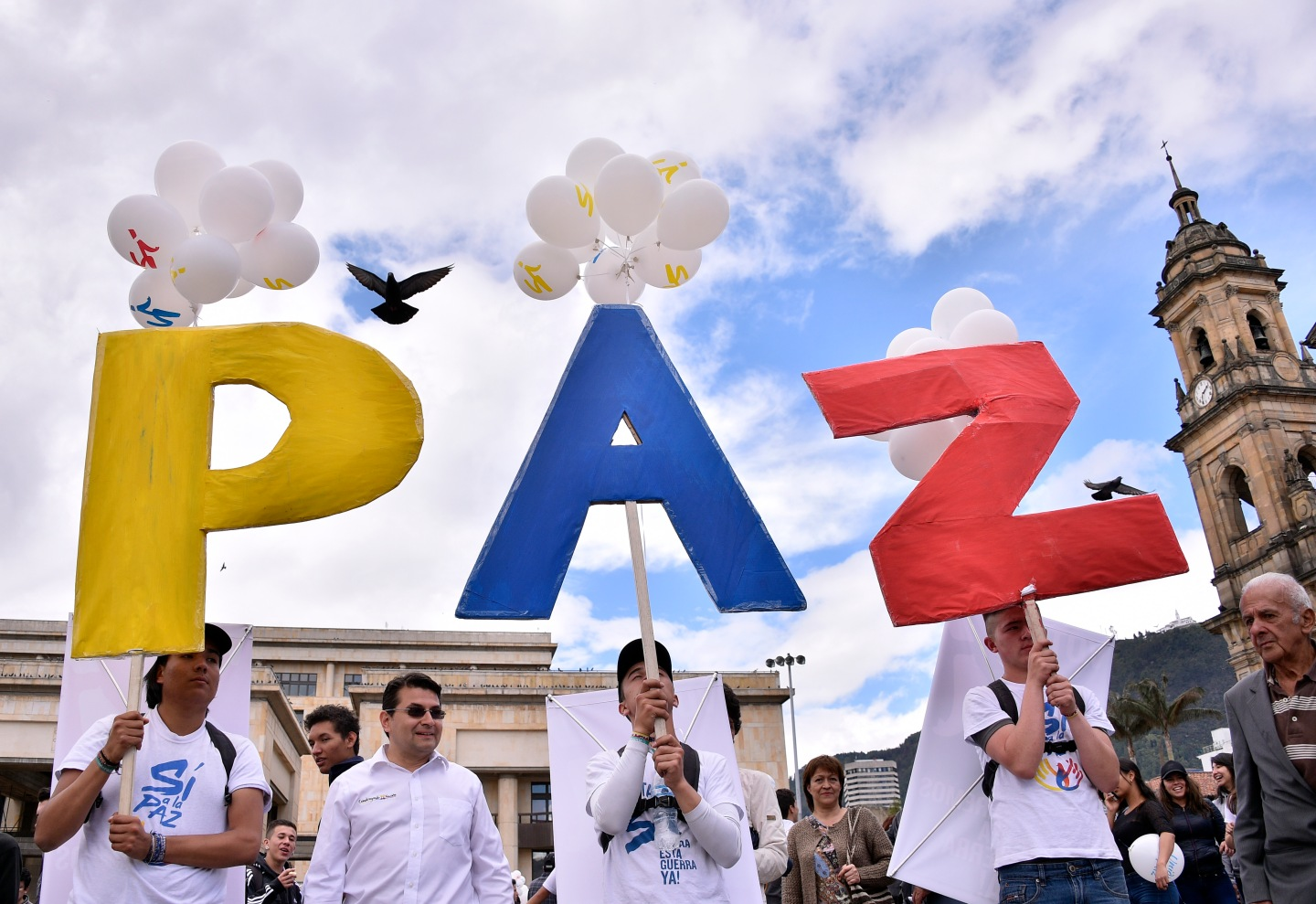"""People gather at Bogota's Bolivar main square on September 26, 2016, to celebrate the historic peace agreement between the Colombian government and the Revolutionary Armed Forces of Colombia (FARC). Colombia will turn the page on a half-century conflict that has stained its modern history with blood when the FARC rebels and the government sign a peace deal on Monday. President Juan Manuel Santos and the leader of the FARC, Rodrigo Londono -- better known by his nom de guerre, Timoleon """"Timochenko"""" Jimenez -- are set to sign the accord at 2200 GMT in a ceremony in the colorful colonial city of Cartagena on the Caribbean coast. / AFP PHOTO / GUILLERMO LEGARIA"""